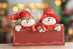 Bonhommes de neige avec le conseil rouge photographie stock libre de droits