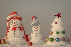 Bonhommes de neige drôles Bonhommes de neige avec les visages souriants dans des chapeaux le jour d'hiver Image stock