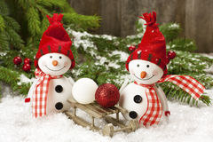 Bonhommes de neige heureux avec le traîneau en bois Images stock