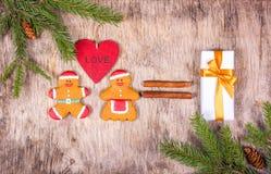 Bonhommes en pain d'épice affectueux Décorations de Noël avec l'arbre de sapin et un cadeau Amour et romance Image stock