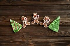 Bonhommes en pain d'épice avec des arbres de Noël de canne et de sucre de sucrerie s'étendant sur le fond en bois brun Images libres de droits