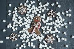 Bonhommes en pain d'épice avec des flocons de neige et des guimauves de canne de sucrerie s'étendant sur le fond en bois gris Noë Photo stock