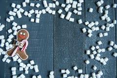 Bonhommes en pain d'épice avec des flocons de neige et des guimauves de canne de sucrerie s'étendant sur le fond en bois gris Noë Image stock