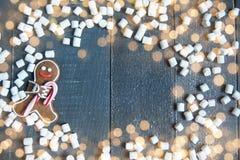 Bonhommes en pain d'épice avec des flocons de neige et des guimauves de canne de sucrerie s'étendant sur le fond en bois gris Noë Images stock