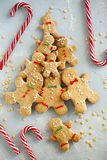 Bonhommes en pain d'épice de sourire faits maison avec une canne de sucrerie sur le fond clair bleu d'étoiles de Noël Vue supérie image libre de droits