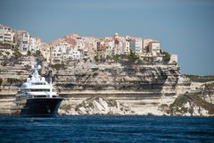 Bonifacio市和峭壁与马达在船锚,可西嘉岛海岛乘快艇 库存图片