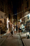 Bonifacio, Corsica. France - 11. August 2014: shopping people in narrow alley by night Royalty Free Stock Images