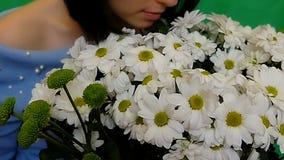 Bonita, a jovem mulher aprecia um ramalhete das flores Camomiles brancos Ame, oferta da mão e coração Fundo verde vídeos de arquivo
