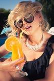 Bonita, suntanned, a jovem mulher bebe o cocktail Fotos de Stock Royalty Free