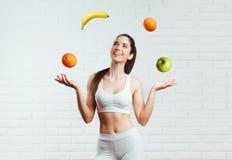 Bonito, ajuste, jovem mulher que entalha com fruto, sobre uma parede de tijolo branca Fotos de Stock