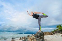 Bonito amadureça a mulher envelhecida que faz a ioga em um beac tropical do deserto imagem de stock