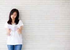 Bonito da felicidade asiática nova da mulher do retrato para relaxar em casa o livro de leitura estando no fundo branco do ciment fotos de stock royalty free