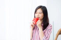 Bonito da mulher asiática nova do retrato com bebida um fundo ereto da janela da cortina da xícara de café imagem de stock
