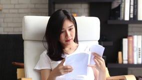 Bonito da mulher asiática nova do retrato relaxe o livro de leitura de assento na sala de visitas em casa, literatura do estudo d video estoque
