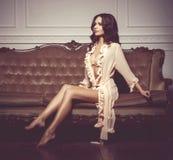Bonito e jovem mulher que levantam na roupa interior 'sexy' no sofá marrom foto de stock royalty free