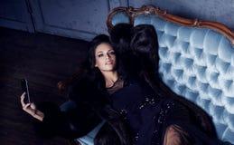Bonito e jovem mulher que levantam no vestido preto no sofá azul vi fotografia de stock royalty free