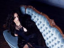 Bonito e jovem mulher que levantam no vestido preto no sofá azul vi imagem de stock