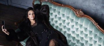 Bonito e jovem mulher que levantam no vestido preto no sofá ciano vi imagem de stock royalty free
