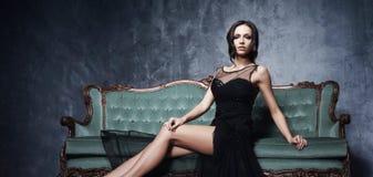 Bonito e jovem mulher que levantam no vestido preto no sofá ciano vi fotos de stock royalty free