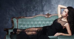Bonito e jovem mulher que levantam no vestido preto no sofá ciano vi imagens de stock