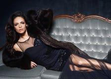 Bonito e jovem mulher que levantam no vestido preto no sofá cinzento vi imagens de stock royalty free