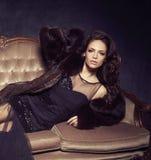 Bonito e jovem mulher que levantam no vestido preto no sofá marrom V imagens de stock