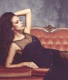 Bonito e jovem mulher que levantam no vestido preto no sofá vermelho Fundo interior e retro do vintage Imagem de Stock