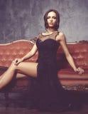 Bonito e jovem mulher que levantam no vestido preto no sofá vermelho vin imagens de stock
