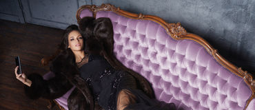 Bonito e jovem mulher que levantam no vestido preto no sofá violeta fotografia de stock royalty free