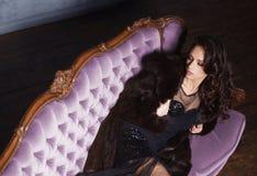 Bonito e jovem mulher que levantam no vestido preto no sofá violeta fotografia de stock