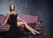 Bonito e moça que levantam no vestido preto no sofá violeta Fundo interior e retro do vintage Fotografia de Stock