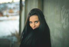 Bonito e mulher no peignoir preto com cabelo longo em uma parede verde das flores e das folhas imagem de stock royalty free