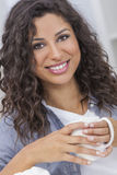 Bonito feliz bebendo de sorriso do chá ou do café da mulher latino-americano Fotografia de Stock Royalty Free