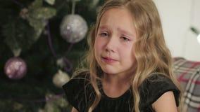 Bonito, menina sentando-se e gritando no fundo da árvore de Natal filme