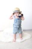 Bonito vestido fashionably 10 meses de bebê com a mala de viagem em ho Fotografia de Stock Royalty Free