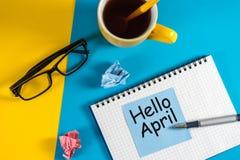 Bonjour avril sur le carnet au lieu de travail photos stock