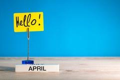 Bonjour avril - un rappel d'inscription de l'arrivée du ` s de mois sur la table, fond bleu, avec l'espace vide pour le texte image libre de droits