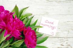 Bonjour ! Bouquet des pivoines roses et la carte blanche avec bonjour inscription ! Photo stock