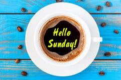 Bonjour concept de tasse de café de dimanche sur le fond bleu avec des haricots Images stock