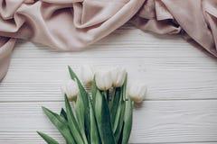 Bonjour configuration d'appartement de ressort tulipes blanches élégantes et fabri doux beige Photographie stock