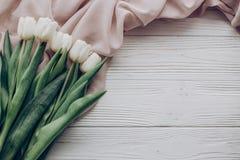 Bonjour configuration d'appartement de ressort tulipes blanches élégantes et fabri doux beige Photos stock