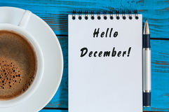 Bonjour décembre écrit sur le bloc-notes près de la tasse de café de matin sur le lieu de travail de directeur ou d'indépendant È Photographie stock