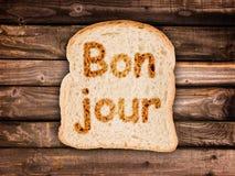 Bonjour de Word écrit sur une tranche de pain grillée Photographie stock