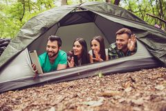 Bonjour des vacances de camp ! Quatre amis joyeux saluent Photos stock