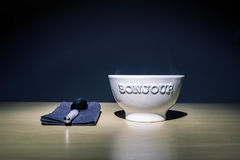 Bonjour Embossed White Ceramic Bowl on Table Beside Stainless Steel Spoon on Black Table Textile Stock Photos