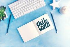 Bonjour graphique d'hiver handlettering dans le carnet ouvert avec le clavier sur la moquerie bleue de configuration d'appartemen Image stock