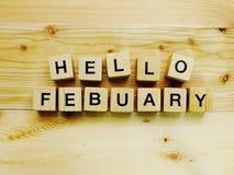 Bonjour lettres en bois d'alphabet de bloc de février sur le fond en bois Photo libre de droits