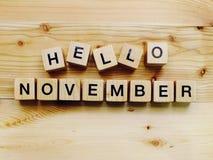 Bonjour lettres en bois d'alphabet de bloc de novembre sur le fond en bois Photographie stock