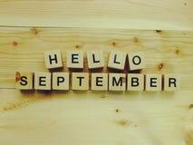 Bonjour lettres en bois d'alphabet de bloc de septembre sur le fond en bois Photos libres de droits