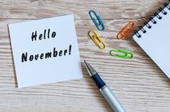 Bonjour novembre lettrage tiré par la main sur le bloc-notes sur le lieu de travail Vue supérieure Images stock